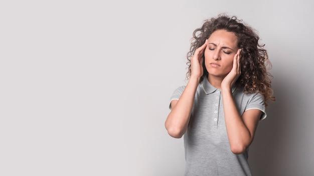 Vrouw met gesloten ogen die aan hoofdpijn tegen grijze achtergrond lijden