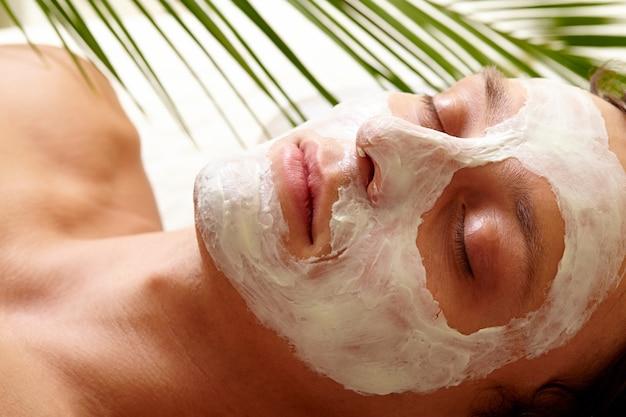 Vrouw met gesloten ogen en crème lotion op gezicht