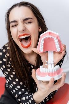 Vrouw met gesloten ogen en geopende mond. jong meisje met geopende educatieve tandartskaak in de buurt van gezicht. tandheelkundig begrip. grappige emoties.
