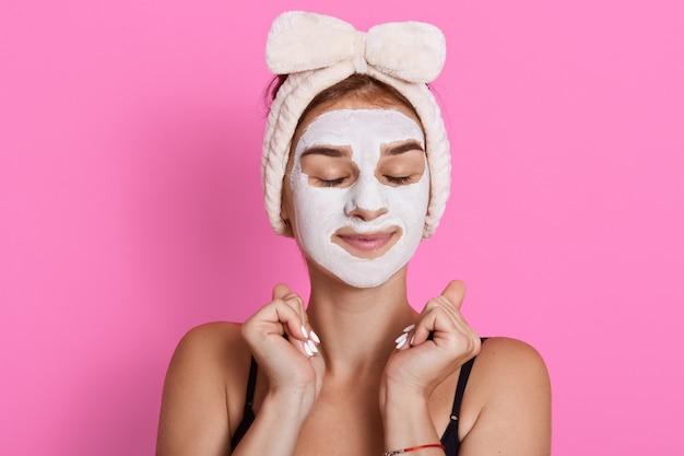 Vrouw met gesloten ogen en wit gezichtsmasker op gezicht, die mouwloos t-shirt en haarband draagt