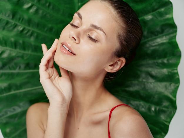 Vrouw met gesloten ogen houdt hand in de buurt van exotisch groen blad