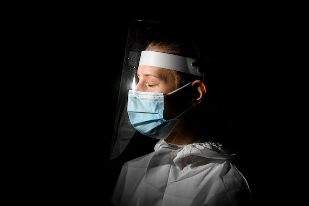 Vrouw met gesloten ogen in medische masker en beschermend schild op haar hoofd