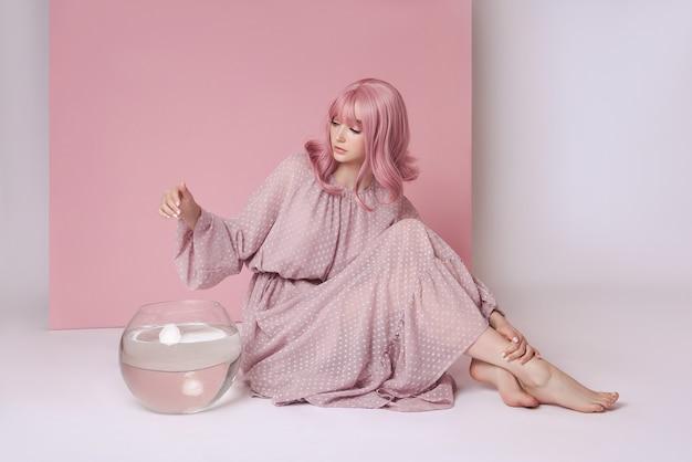 Vrouw met geverfd roze haar in lange jurk zittend op de vloer