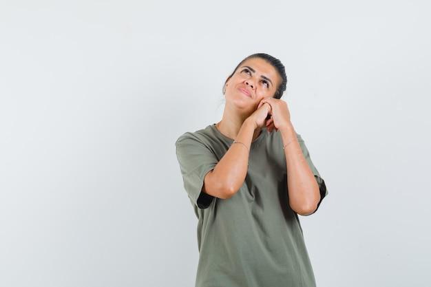 Vrouw met gevouwen handen op de wang in t-shirt en op zoek dromerig