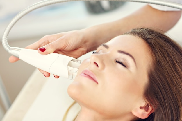 Vrouw met gezichtsbehandeling in schoonheidssalon
