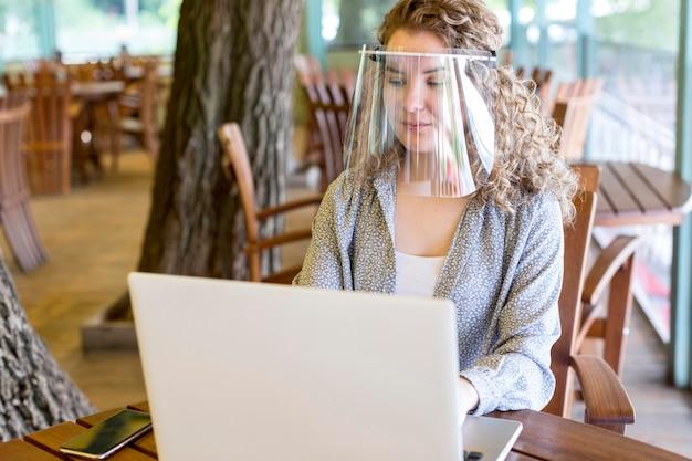 Vrouw met gezichtsbescherming tijdens het werken op laptop