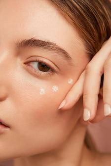 Vrouw met gezichtscrème close-up