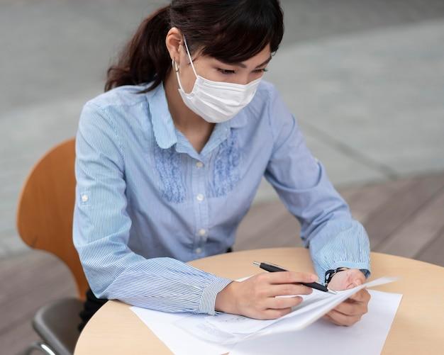 Vrouw met gezichtsmasker aan tafel