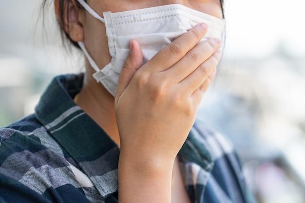 Vrouw met gezichtsmasker beschermt filter tegen luchtvervuiling (pm2.5)