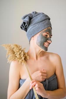 Vrouw met gezichtsmasker bij het stellen met bloem