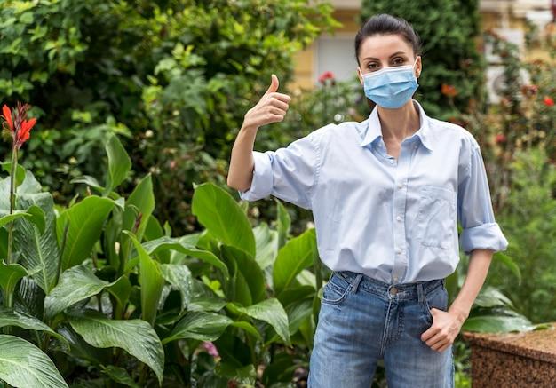 Vrouw met gezichtsmasker dat de duimen toont ondertekent omhoog met exemplaarruimte