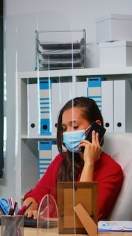Vrouw met gezichtsmasker die aan de telefoon praat en naar het bureaublad kijkt en de statistieken analyseert. freelancer die op de werkplek aan het chatten is met een team op afstand dat op een smartphone achter de computer spreekt