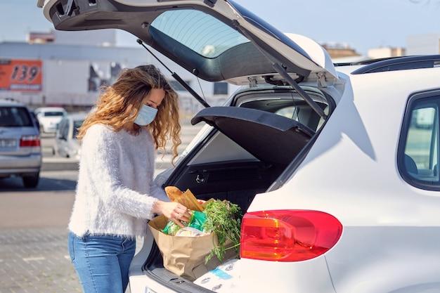 Vrouw met gezichtsmasker die boodschappentassen in de kofferbak van de auto plaatst