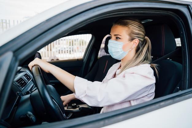 Vrouw met gezichtsmasker die haar auto drijven tijdens pandemie van het coronavirus