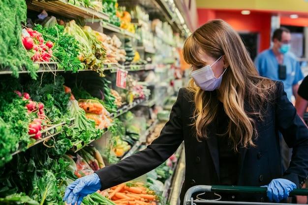 Vrouw met gezichtsmasker die latexhandschoenen draagt tijdens het winkelen in een supermarkt tijdens de quarantaine van het coronavirus