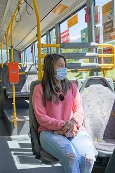 Vrouw met gezichtsmasker die met de bus door de stad reist