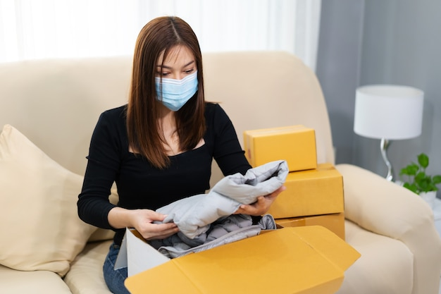 Vrouw met gezichtsmasker die thuis een kartonnen pakjesdoos opent tijdens de coronavirus-pandemie
