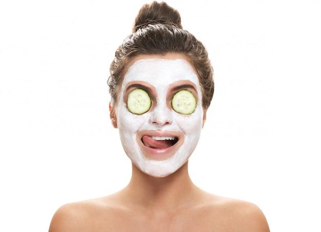 Vrouw met gezichtsmasker en komkommerplakken op haar ogen