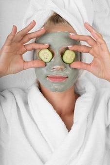 Vrouw met gezichtsmasker en plakjes komkommer