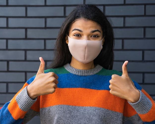 Vrouw met gezichtsmasker en sociaal afstandsconcept