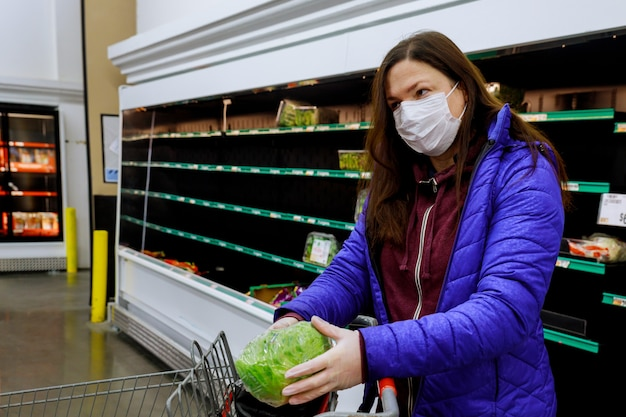 Vrouw met gezichtsmasker het kopen sla bij supermarkt met lege planken.