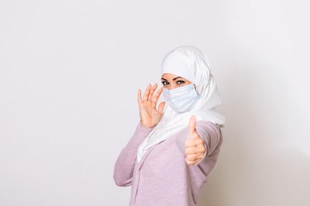 Vrouw met gezichtsmasker in hijab, bescherming van coronavirus in menselijke longen.
