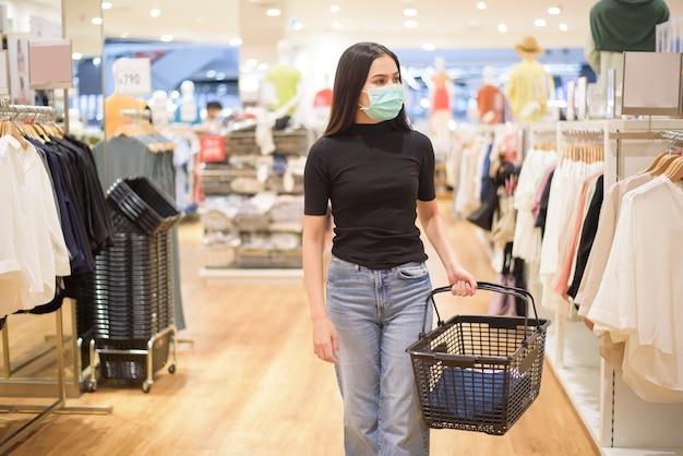 Vrouw met gezichtsmasker is winkelen kleding in winkelcentrum