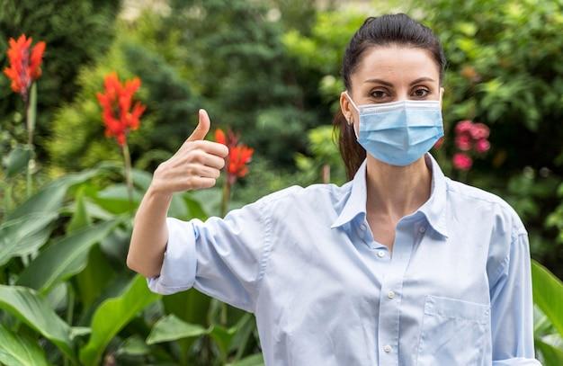 Vrouw met gezichtsmasker met de duimen omhoog teken