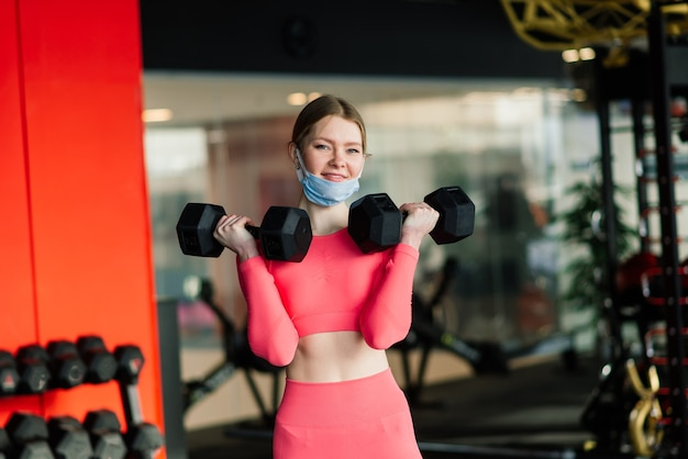 Vrouw met gezichtsmasker oefeningstraining in de sportschool tijdens pandermic van het coronavirus.