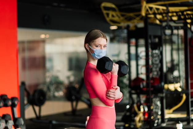 Vrouw met gezichtsmasker oefentraining in de sportschool tijdens pandermic van het coronavirus, covid