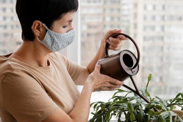 Vrouw met gezichtsmasker planten binnenshuis water geven