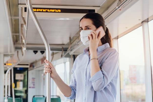 Vrouw met gezichtsmasker praten aan de telefoon tijdens het reizen met het openbaar vervoer