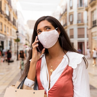 Vrouw met gezichtsmasker praten aan de telefoon