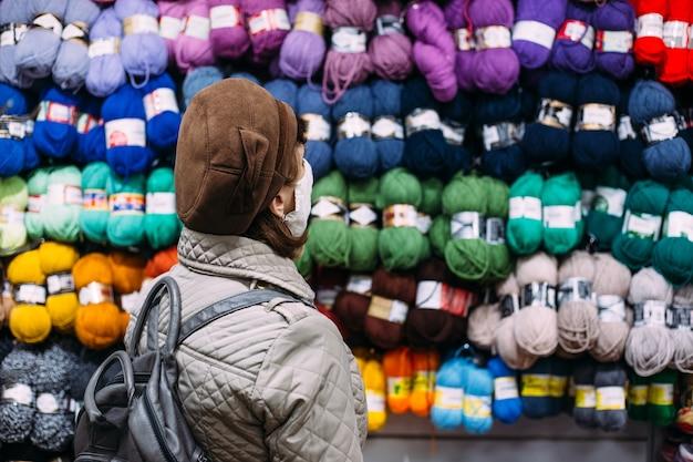 Vrouw met gezichtsmasker selecteert garenproducten in een winkelconcept voor handwerkwinkels