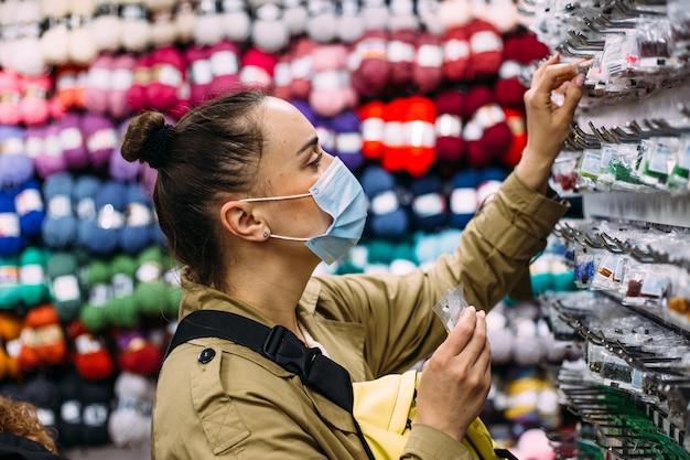Vrouw met gezichtsmasker selecteert kralenproducten in het winkelconcept van de handwerkwinkel