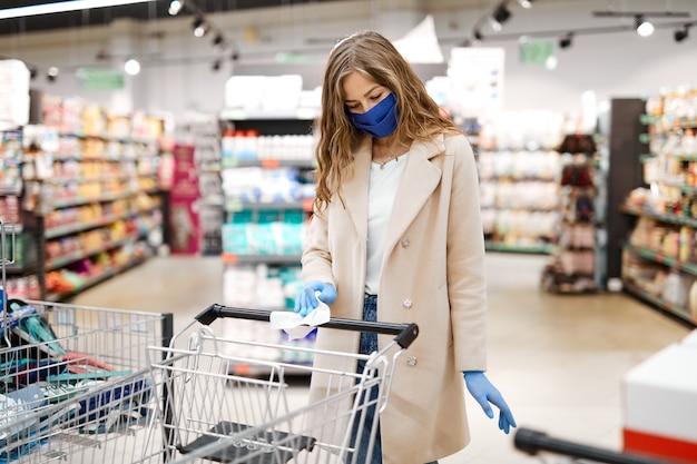 Vrouw met gezichtsmasker veegt het handvat van de winkelwagen af met een desinfecterende doek in de supermarkt.