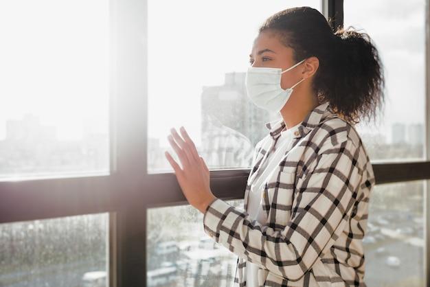 Vrouw met gezichtsmasker wil graag het huis uit. concept van pandemie van covid-19 coronavirus