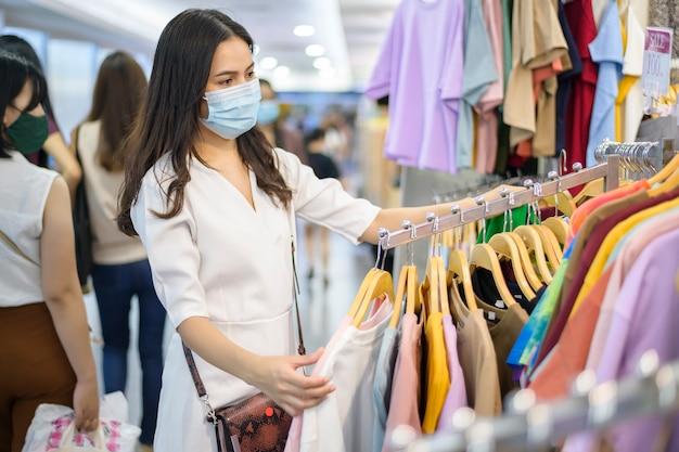 Vrouw met gezichtsmasker winkelt kleding in winkelcentrum