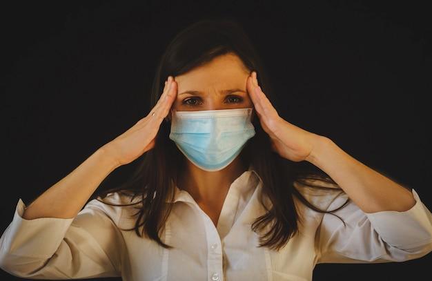 Vrouw met gezichtsmasker ziek en hoofdpijn jonge brunette met blote schouders die tempels aanraakt
