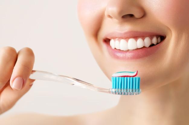 Vrouw met gezonde witte tanden houdt een tandenborstel en glimlacht.