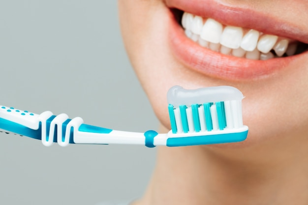 Vrouw met gezonde witte tanden houdt een tandenborstel vast en glimlacht mondhygiëneconcept