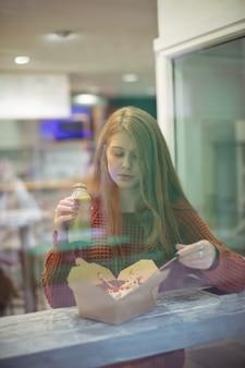 Vrouw met gezondheidsdrank die salade eet