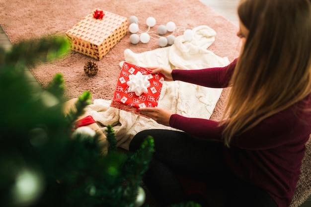 Vrouw met giftdoos dichtbij winkelhaak, feelichten en kerstboom