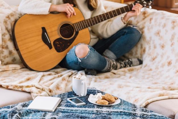 Vrouw met gitaar dichtbij lijst met smartphone, blocnote, kop van drank en koekjes