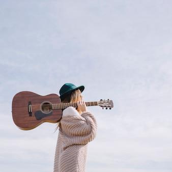 Vrouw met gitaar op achtergrond van hemel