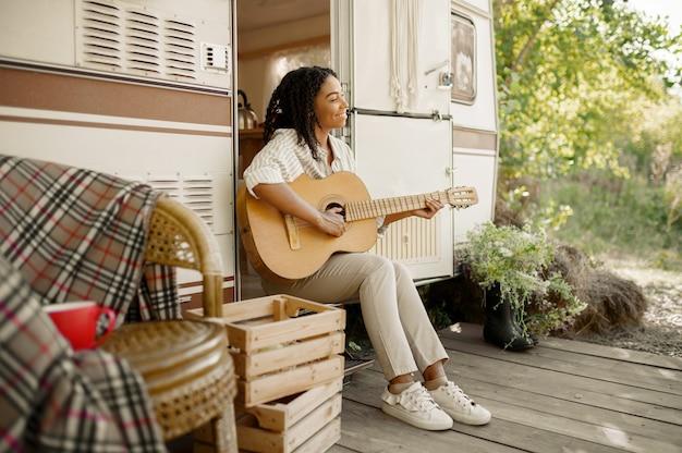 Vrouw met gitaar zittend bij de ingang van de camper, kamperend in een aanhangwagen. stel reist op busje, vakanties op camper