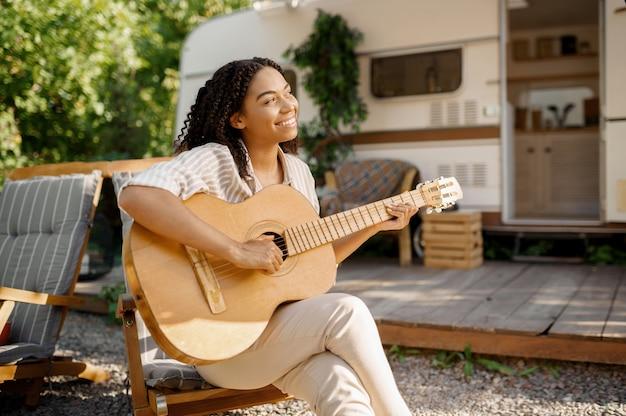 Vrouw met gitaar zittend in de buurt van de camper, kamperend in een aanhangwagen. stel reist op busje, vakanties op camper