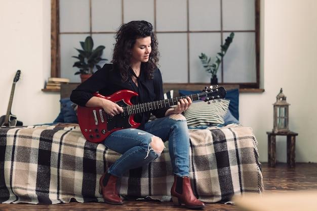 Vrouw met gitaar zittend op bed