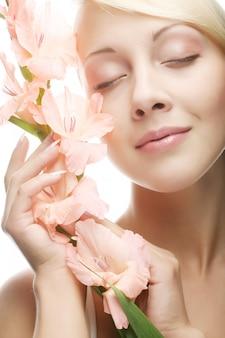 Vrouw met gladiolenbloemen in haar handen