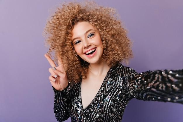 Vrouw met glanzende schaduwen en blonde krullen, topje in pailletten draagt, toont vredesteken en maakt selfie op paarse ruimte.